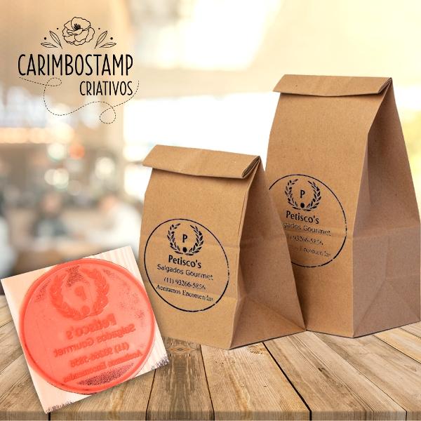 foto com carimbo e duas sacolas kraft estampas pelo carimbo